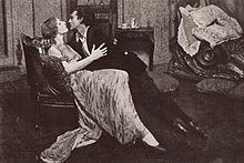 Violet Kemble-Cooper and John Barrymore half-sitting, half-lying in an eager embrace on a couch, about to kiss