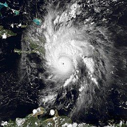 Satellite image of a mature hurricane. The storm features a small, but prominent eye and the whole system covers most of the eastern Caribbean Sea. Haiti can be seen along the edge of a feeder band and eastern Cuba is also visible on the left side of the image.