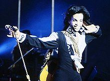 Prince, in a frock and jacket, smiles with a hand to his left ear.