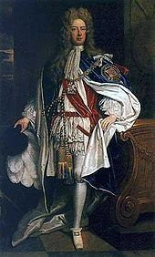A man in robes of the Order of the Garter. The man is wearing white and red clothing, with a mantle adorned with a large badge