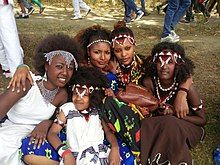 This photo represents the varieties of dressing and hairstyle of the Oromo culture. the kid sitting in front of the group dressed Guji Oromo clothes. the four girls at the back from left to right, dressed Harar, Kamise, Borena and Showa styles and all are Oromo style