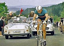 A man on a bicycle, with a car behind him.