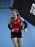 woman in sports gear with a volleyball under her arm