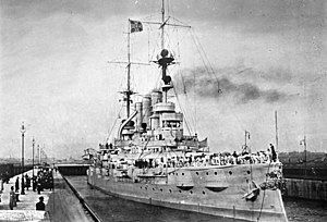 A large gray battleship sits in a lock, crew members in white uniforms crowd the ship's deck