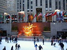 Ice skaters on a rink below a golden sculpture and a row of national flags that fly in front of a stone tower.