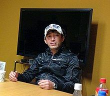 A man sitting at a table in front of a television. He is wearing a jacket and a hat and looking toward the camera.