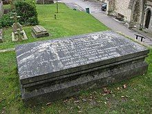 Photograph of a coffin-shaped granite tomb.