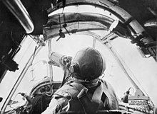 Pilot in a small cockpit. He is wearing a parachute and leather helmet. This is a still from movie footage shot by Damien Parer.