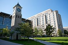 Two modern glass and concrete building side by side in front of an open grass lawn which has a short clocktower on the left side.