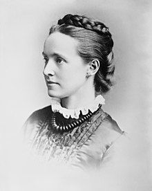 A black and white left profile formal photograph of a woman