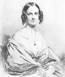 Three quarter length portrait of woman aged about 30, with dark hair in centre parting straight on top, then falling in curls on each side. She smiles pleasantly and is wearing an open necked blouse with a large shawl pulled over her arms