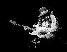 """A black and white photograph of Jimi Hendrix playing a Fender Stratocaster electric guitar (during his """"hat phase"""" in 1968)."""