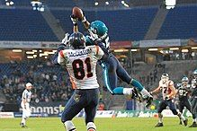 A defensive player leaps into the air in front of a receiver and intercepts the pass