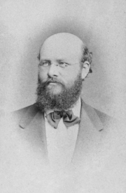 A photograph of a bearded white man with male-pattern baldness wearing glasses