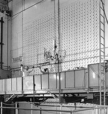 两名工人站在一个移动平台上,将一根棒状物体插入面前一堵满是小孔的墙中。