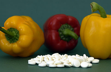 Two yellow and one red pepper with dozens of 500 mg white vitamin tablets in front of them