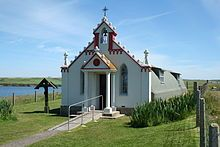 A small chapel sits in green fields under a blue sky. A body of water lies to the left. The front of the building is painted red and white and is decorated with colonnades and a small bell tower. By contrast, the main part of the building is painted grey and has a curved exterior reminiscent of a Nissen hut.