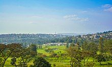 Panorama photograph with the greens and buildings of the golf club visible, as well as hills and houses in the distance