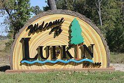 """""""欢迎来到拉夫金""""展牌,附在原木条纹的雕刻上,显示木材行业在此地的重要性"""