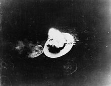 Black and white photo of a large explosion on a body of water