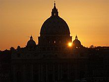The dark silhouette of St. Peter's dome set against the orange, evening sky and setting sun.