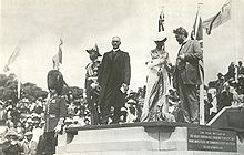 Five people on stone platform, from left: Man with mustache in military dress uniform and bushy tall black hat with chinstrap; man in military uniform with many medals and old fashioned naval officer's hat; man with white hair in suit with long dark coat and white collar; woman in Victorian dress with white hat; man with beard and wild hair in suit. Crowd and flags in background.