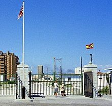 Two women standing at a closed line of gates, with the British and Spanish flags flying on separate poles on either side.