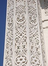 A white column with ornate designs carved into it, including a Star of David