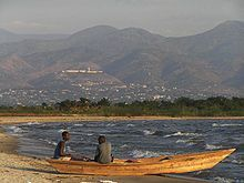 two sitting in skiff on beach on lakeshore with mountains in bckround