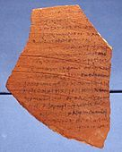 A fragment of teracotta pottery, written on with black ink.
