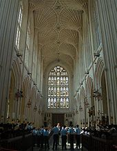 Interior of large building with a stained glass window at the far end. Above is a barrel vault ceiling and on either side rows of arches. People standing at the bottom of the picture dwarfed by the height of the ceiling.