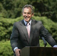 A smiling man with grey hearing wearing a dark suit, standing behind a podium