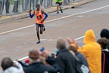 Black man wearing blue arm sleeves, navy shorts and orange sleeveless shirt printed number 2, running down paved street as fans behind barricade cheer him on in foreground