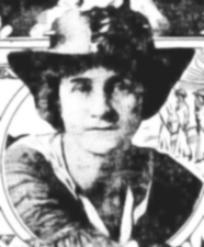 A black-and-white photograph of a woman in a boater-style hat