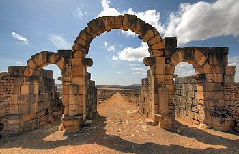 View through a triple-arched gate looking downhill to a street lined with ruins