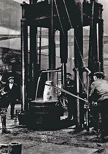 Workers stand around a large forge, where a shell burns red-hot.