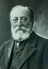 bust-length portrait of Saint-Saëns with a beard in a vest and suit, looking at the viewer