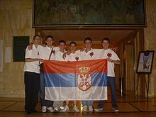 Six boys, standing on a line, all wearing white tops with red logos on their chest. They are holding a red, blue and white striped flag, which features a prominent crown and coat of arms.
