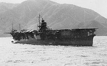 Photograph of a ship floating in the ocean taken from a location on the ocean surface some distance away. The upper deck of the ship is flat except for a superstructure visible near the center of the ship. The shoreline and some mountainous terrain are visible in the distance behind the ship; the sky is visible above the mountains.