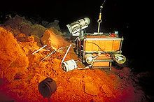 A small box-like robot positioned on orange rocks