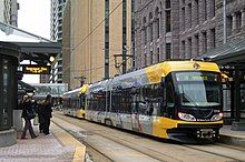 Yellow light rail across the street from old city hall downtown