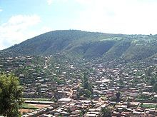 Panorama photograph showing houses in foreground, with Mount Kigali in the background