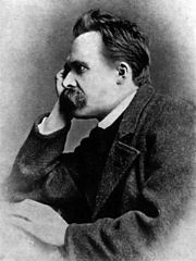 A moustachioed man in his late thirties looks to the left of the photo. His head rests on his far hand.