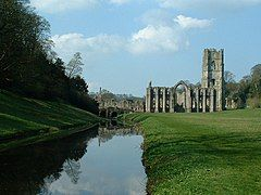 A photograph of a ruined abbey; a river passes by in the lower left hand of the picture, overhung with dark trees. A ruined abbey building in stone makes up the midground of the right side of the photograph.