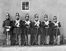 black & white photograph of six U.S. marines standing in line, five with Civil War-era rifles and one with an NCO sword.