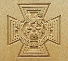 The cross pattée bearing the crown of Saint Edward surmounted by a lion with the inscription FOR VALOUR etched into stone.