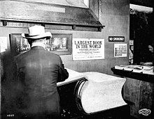 """An extremely large book rests on a table, with its front cover and a small portion of its pages flipped open to the left. A man facing away from the camera stands in front of the flipped part. On the wall above the book is a sign saying """"LARGEST BOOK IN THE WORLD - VISITORS' REGISTER FOR CALIFORNIA BUILDING - Alaska–Yukon–Pacific Exposition […]"""". On a table in the background and to the right of the large book is another table on which many small stacks of normal-sized books are visible."""