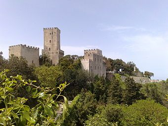 A castle with a tall narrow tower and walls topped by battlements stretches along the edge of a cliff covered in trees and palm trees