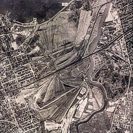 "George Wilson and his wife Myrtle live in the ""valley of ashes,"" a refuse dump (shown in the above photograph) historically located in New York City during the 1920s. Today, the area is Flushing Meadows–Corona Park."