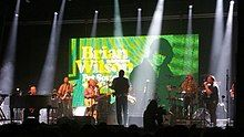 Wilson's large band onstage in front of an LED screen showing photos from the Pet Sounds era